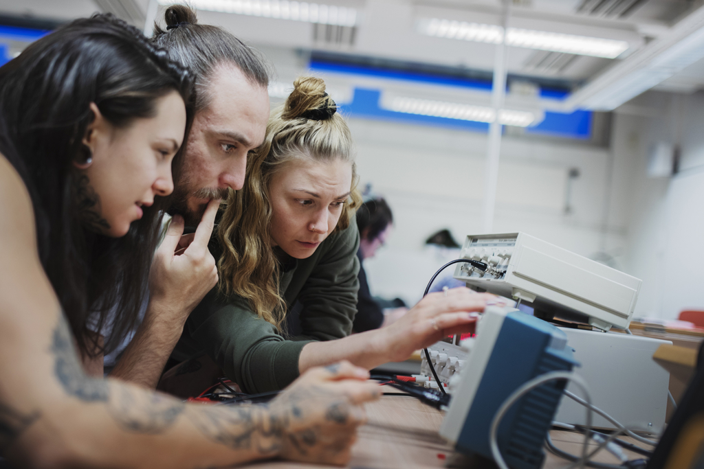 Tre studerande, två kvinnor och en man, arbetar koncentrerat med elektronik.