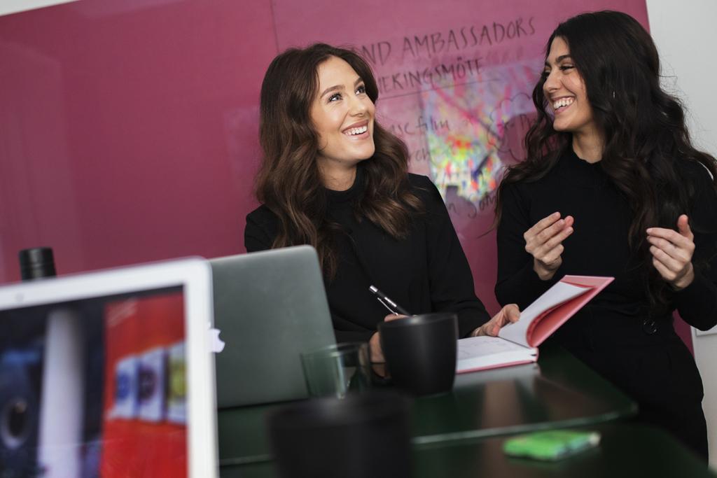 Två kvinnor står vid ett bord med datorer och anteckningsblock och skrattar mot varandra.