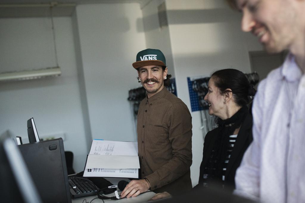 Två män och en kvinna ser glada ut och arbetar med datorer och håller i en bok.