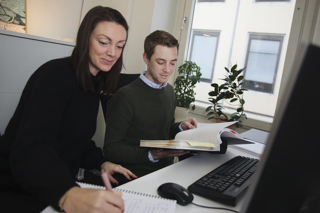 En man och en kvinna sitter framför en dator. Kbinnan antecknar i ett block och mannen håller i en pärm.