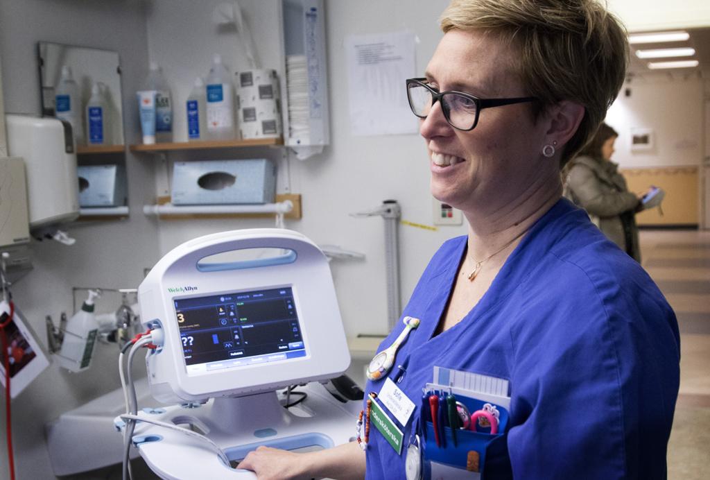 Kvinnlig undersköterska står vid en EKG-maskin i sjukhusmiljö.