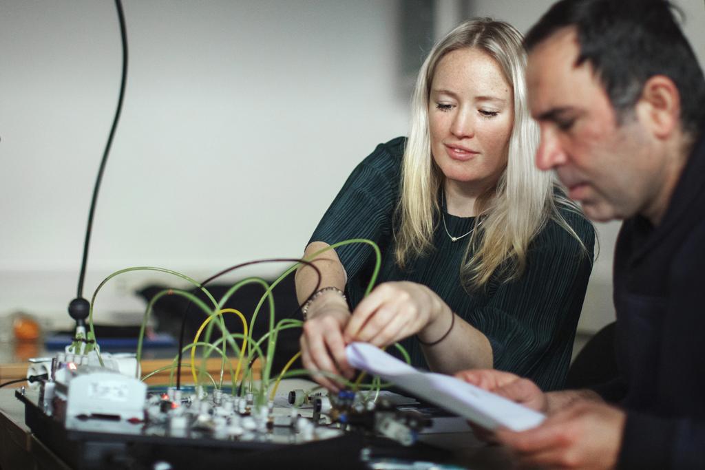 Två studerande, en kvinna och en man, arbetar med sladdar och elektronik.