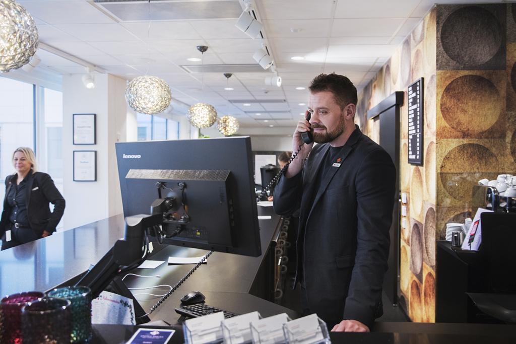 En man står i en reception och pratar i telefon.