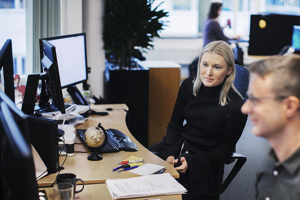 Ung kvinna sitter i kontorslandskap och tittar in i en datorskärm.