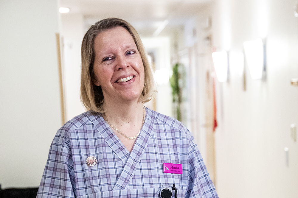 En kvinnlig undersköterska som ser glad ut och tittar in i kameran.