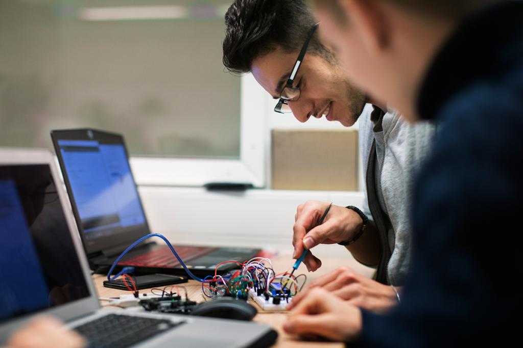 Två manliga studerande sitter vid varsin dator samtidigt som de arbetar med ett kretskort.