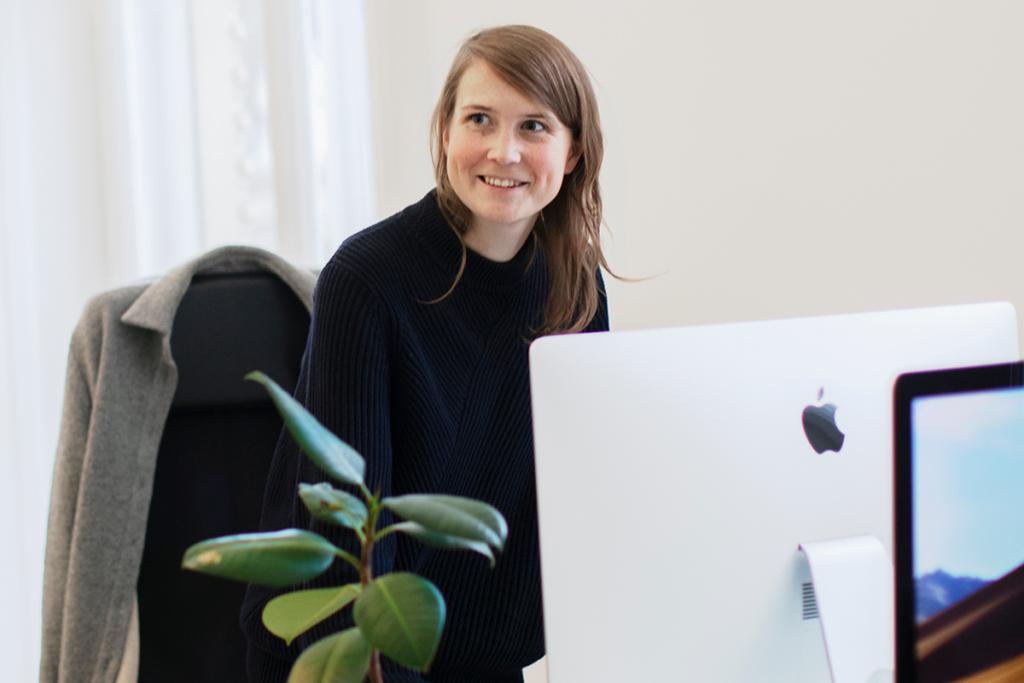 Leende kvinna står framför en dator.