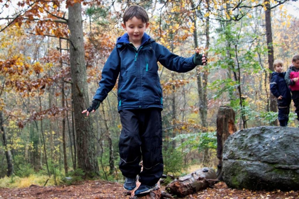 Ung pojke balanserar på en stock i skogen
