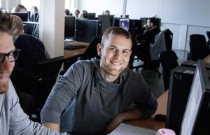 Manlig studerande sitter framför en dator, tittar in i kameran och ler.